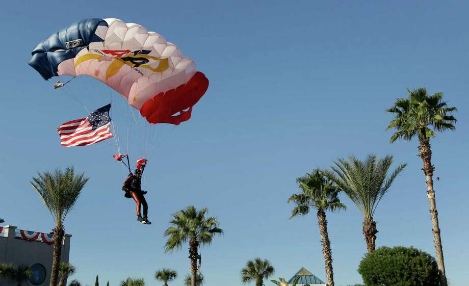 The Veteran Parachute Jump Team demonstration was just one of the activities at the annual Salute to Military Service held at the Kemah Boardwalk. In this photo, Mario Rivera, a retired Army veteran, carries the U.S. flag while landing. Photo: Melissa Phillip, Houston Chronicle / © 2014  Houston Chronicle