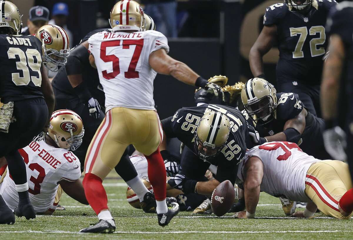 New Orleans Saints center Jonathan Goodwin (55) and San Francisco 49ers defensive end Justin Smith dive for a Drew Brees fumble, recovered by the 49ers, in overtime.