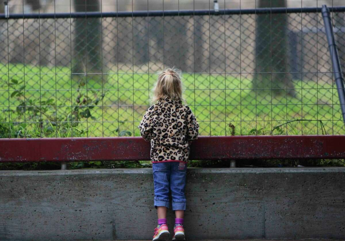 A girl looks at animals through a fence near the entrance of the San Francisco Zoo.