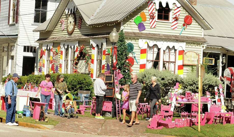 Joe Birchum, of Spring, far left, watches his pink baby doll furniture as shoppers walk past during the 33rd Annual Home for the Holidays in Old Town Spring. The event is scheduled for every weekend between November 8- December 24th. Family friendly activities, display of lights, trackless train rides, and photos with Santa are part of the activities. Photo: David Hopper, Freelance / freelance