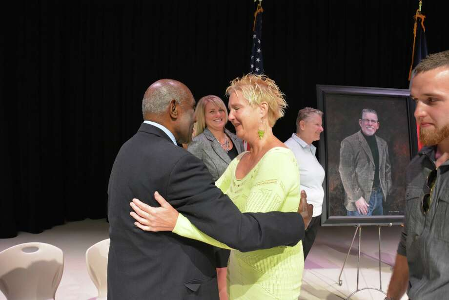 Roosevelt Alexander, retired educator and namesake of Roosevelt Alexander Elementary School, hugs widow Janet Randolph after the dedication of James Randolph Elementary, which is named after her husband. In the background are Randolph Elementary principal Kristin Harper and James Randolph's sister, Nicki. Photo: Courtesy Katy ISD