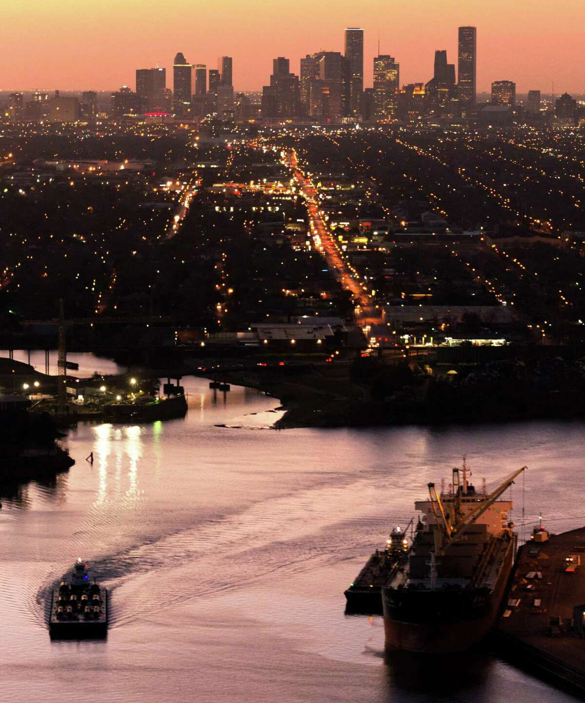 The Houston skyline is seen behind traffic on the Ship Channel. A commercial resources firm says its analysis of economic data shows Texas is doing the third-best job rebounding from the Great Recession.