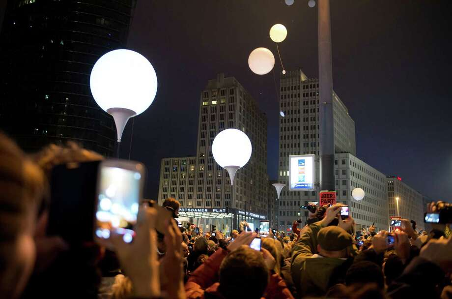 """Balloons of the art installation """"Lichtgrenze 2014"""" fly away at Potsdamer Platz to com-memorate the 25th anniversary of the Nov. 9, 1989 fall of the Berlin Wall on Sunday. """"For peace and freedom,"""" said mayor Klaus Wowereit. Photo: Soeren Stache, SUB / dpa"""