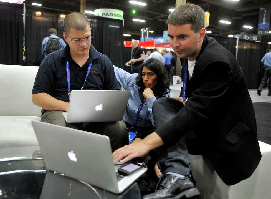 Arxan Technologies' Joe Abbey, from left, Jodi Wadhwa and Jonathan Carter prepare for a hacking demonstration at the Black Hat USA 2014 conference in August. Photo: DAVID BECKER, FRE / FR170737 AP