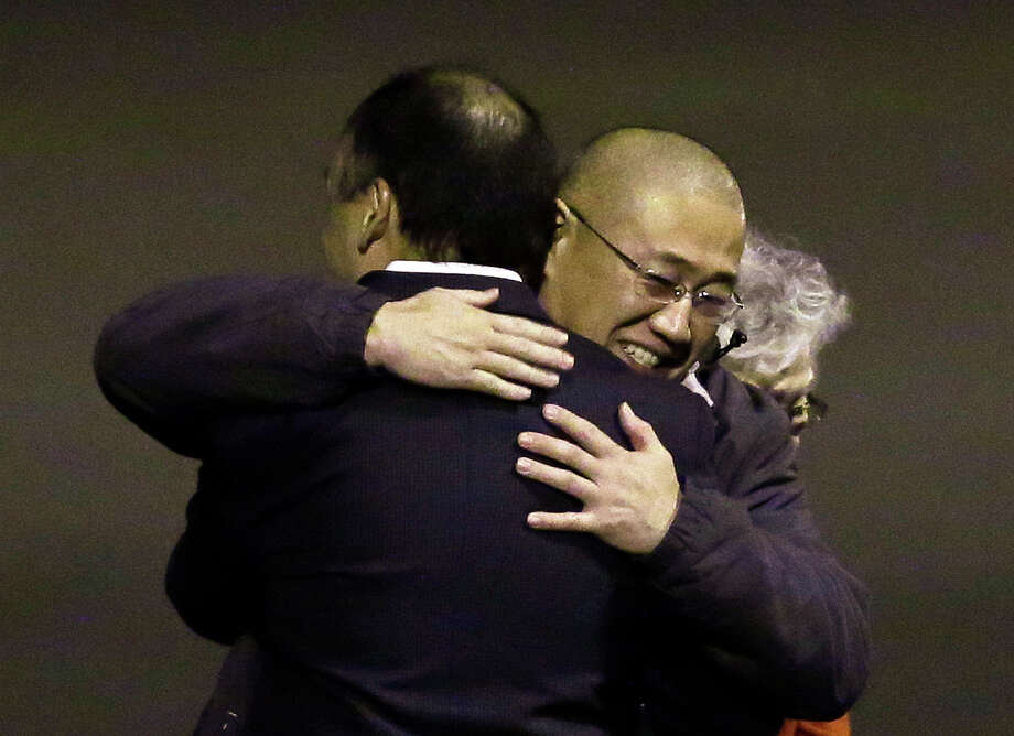 Kenneth Bae, center, who had been held in North Korea since 2012, arrived in the U.S. on Saturday at a Washington state military base. Photo: Ted S. Warren, STF / AP