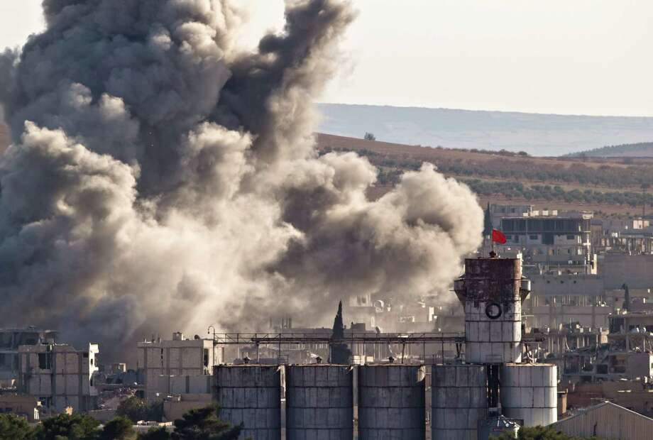 The Turkish flag flies on a grain silo backdropped by smoke in the Syrian town of Kobani, after an airstrike by the U.S. coalition, seen from the border with Syria. Photo: Vadim Ghirda, STR / AP