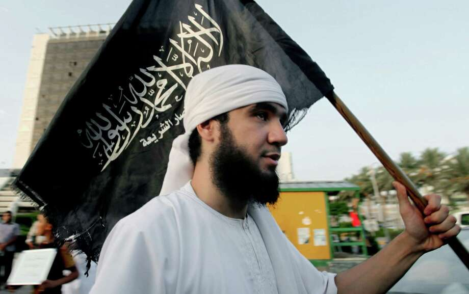 "FILE - In this Sept. 14, 2012, a Libyan follower of Ansar al-Shariah Brigades carries the Brigades' flag with Arabic writing that reads, ""There is no god but Allah and Muhammad is his messenger, Ansar al-Shariah,"" during a protest in front of the Tibesti Hotel in Benghazi, Libya. On Friday, Oct. 31, 2014, bearded militants gathered at a stage strung with colorful lights in Darna, a Mediterranean coastal city long notorious as Libya's center for jihadi radicals. With a roaring chant, they pledged their allegiance to the leader of the Islamic State group. Many of Darna's militants joined, though some didn't. Part of Ansar al-Shariah, one of the country's most powerful Islamic factions, joined while another part rejected it. (AP Photo/Mohammad Hannon, File) ORG XMIT: CAITH101 Photo: Mohammad Hannon / AP"