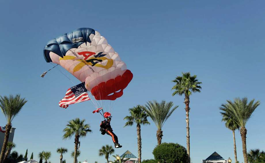 Retired Army veteran Mario Rivera carries the U.S. flag during a parachute jump at the Salute to Military Service at the Kemah Boardwalk. Photo: Melissa Phillip, Staff / © 2014  Houston Chronicle