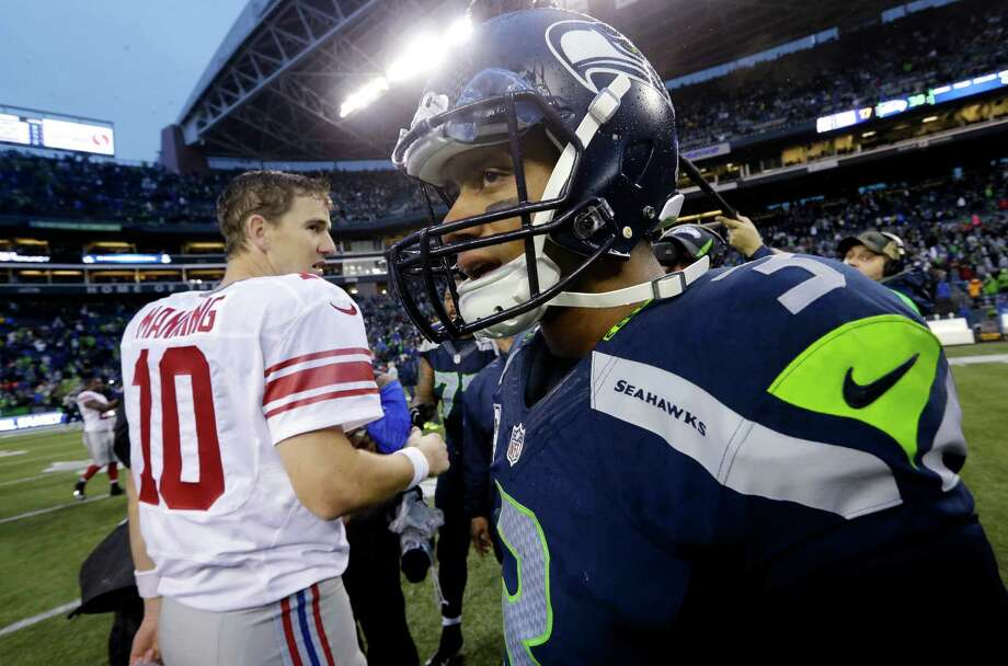 Seattle Seahawks quarterback Russell Wilson, right, turns away after greeting New York Giants quarterback Eli Manning after an NFL football game, Sunday, Nov. 9, 2014, in Seattle. The Seahawks won 38-17. (AP Photo/Elaine Thompson) ORG XMIT: SEA154 Photo: Elaine Thompson / AP