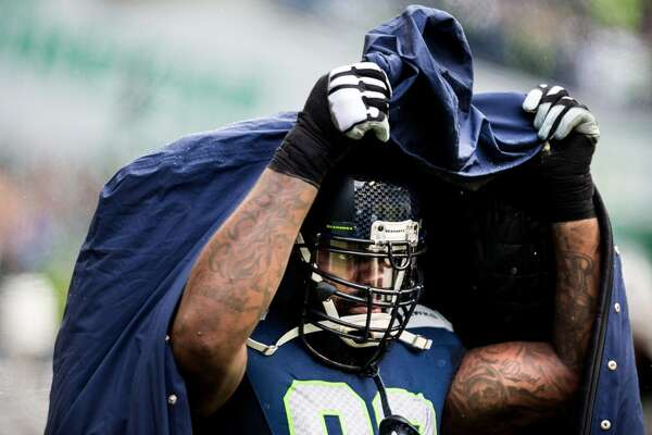 Seahawks player Tony McDaniel pulls a jacket over his head to protect from rain.