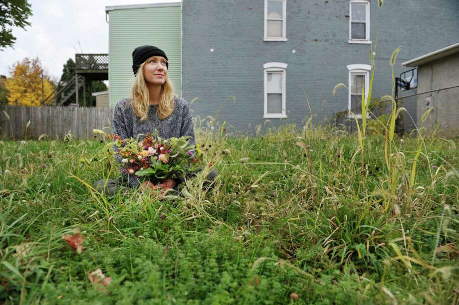 Colie Collen holds flowers as she sits in the empty lot at 118 Jefferson St. on Wednesday, Nov. 5, 2014, in Troy, N.Y.  Collen is buying the empty lot to turn it into a flower garden for her flower business Flower Scout.  (Paul Buckowski / Times Union) Photo: Paul Buckowski / 00029339A
