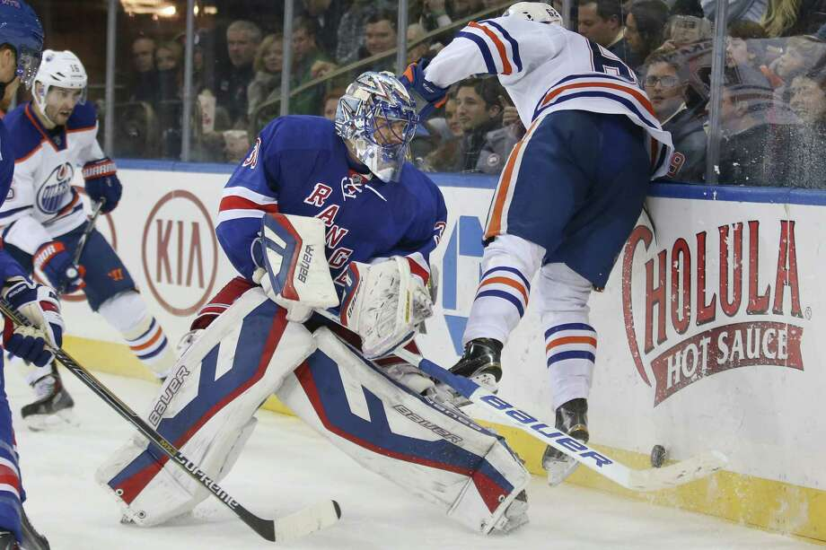 New York Rangers goalie Henrik Lundqvist (30) attempts to clear the puck as Edmonton Oilers right wing Iiro Pakarinen (62) avoids a collision during the third period of an NHL hockey game at Madison Square Garden, Sunday, Nov. 9, 2014, in New York. The Oilers won 3-1. (AP Photo/John Minchillo) ORG XMIT: MSG116 Photo: John Minchillo / FR170537 AP