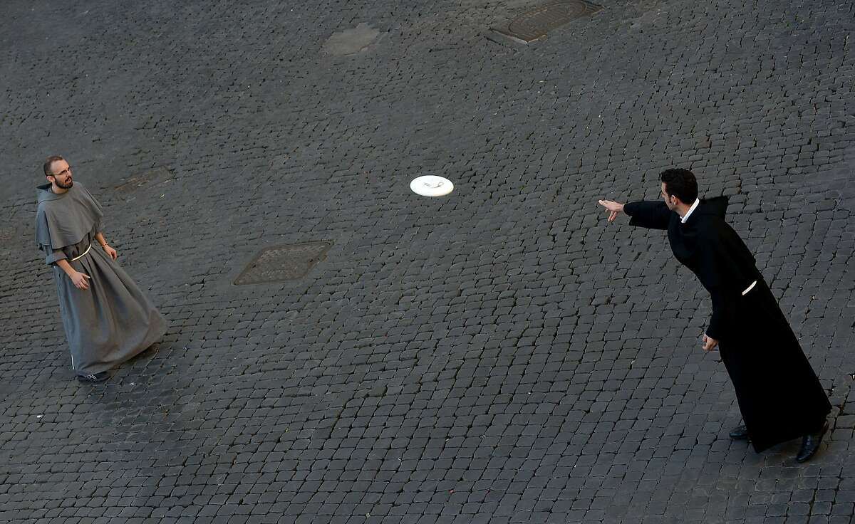 TOPSHOTS Friars play frisbee at Piazza Santi Apostoli on November 9, 2014 in Rome. AFP PHOTO / TIZIANA FABITIZIANA FABI/AFP/Getty Images