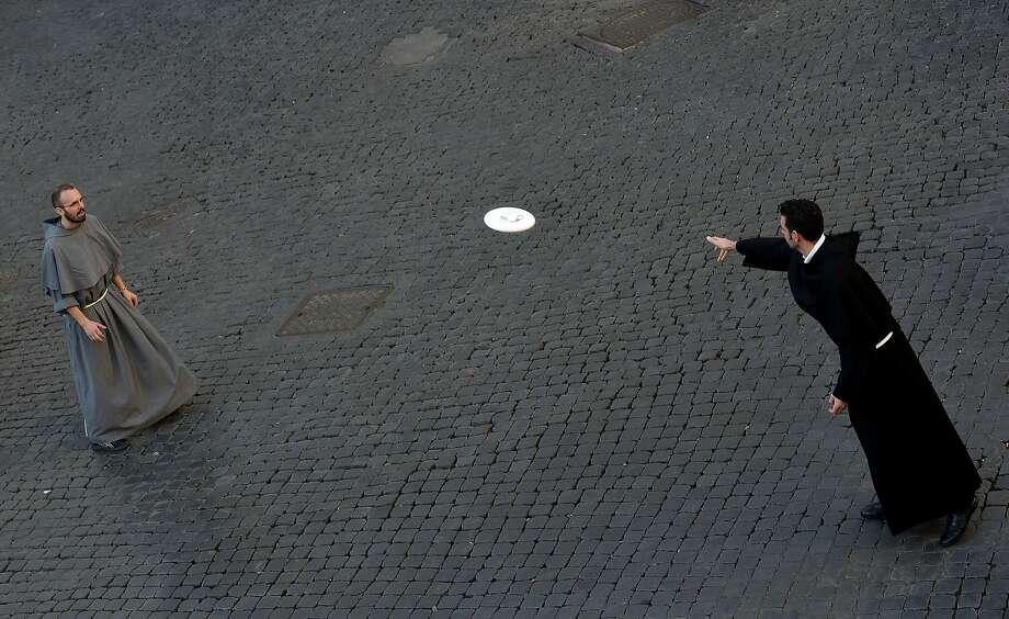 TOPSHOTS Friars play frisbee at Piazza Santi Apostoli on November 9, 2014 in Rome.   AFP PHOTO / TIZIANA FABITIZIANA FABI/AFP/Getty Images Photo: Tiziana Fabi, AFP/Getty Images