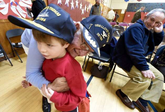 Korean war veteran Capt. Miller hugs his step-grandson Jackson Oaks at the Brown School Veterans Day ceremony on Monday, Nov. 10, 2014. (Skip Dickstein/Times Union)