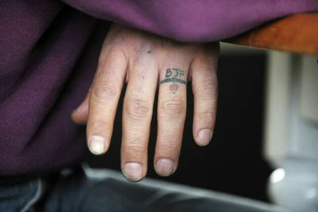 A tattoo resembling a wedding ring and including the  initials of a former girlfriend, Brianne Frolke, is seen on Edward Leon's hand during an interview with Leon Monday, March 3, 2014 in St. Johnsville, NY.   (Paul Buckowski / Times Union) ORG XMIT: MER2014030316163381 Photo: Paul Buckowski / 00025921A