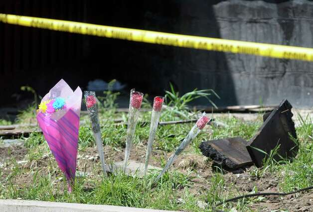 Flowers are placed on the curb at the scene of a house fire at 438 Hulett St. on Thursday, May 2, 2013 in Schenectady, NY.  Police said that four of the five people pulled from a burning home early Thursday morning  have died.  Three children and one adult died.   (Paul Buckowski / Times Union) Photo: Paul Buckowski / 10022261A