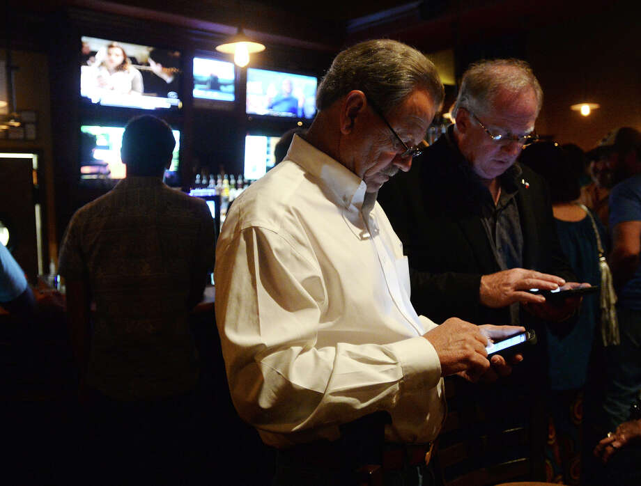 Rick Williams, candidate for 172nd district court judge, front, and Billy Oliver check the numbers during Tuesday's watch party at Madison's. Beaumont Republican party candidates held watch parties at Madison's, Tradewinds, and Carlito's on Tuesday evening. Photo taken Tuesday 11/4/14 Jake Daniels/@JakeD_in_SETX Photo: Jake Daniels / ©2014 The Beaumont Enterprise/Jake Daniels