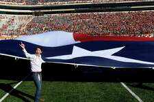 AUSTIN, TX - NOVEMBER 8: Members of Alpha Phi Omega handle the world's largest Texas flag during the pre-game ceremonies of the NCAA Big 12 game between the Texas Longhorns and the West Virginia Mountaineers on November 8, 2014 at Darrell K. Royal-Texas Memorial Stadium in Austin, Texas. Texas beat West Virginia 33-16.