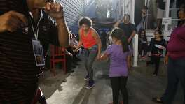 Andrea Rodriguez (center in red) dances with family and friends in the backyard of the Mosqueda family home at the Mosqueda family farewell party on Saturday,  August 23,  2014 in San Francisco, Calif.