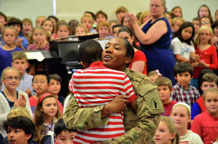 Spc. Crystal Merise, of the U.S. Army, surprised her son Sincere Francois during the Hindley Elementary School Veterans' Day Ceremony. She had just come home early from a year-long tour in Afghanistan and wasn't supposed to be home until the day before Thanksgiving. Photo: Megan Spicer / Darien News
