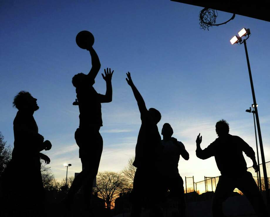 Young men play a pick-up game of basketball in Washington Park as the sun goes down on Monday, Nov. 10, 2014 in Albany, N.Y.  (Lori Van Buren / Times Union) Photo: Lori Van Buren