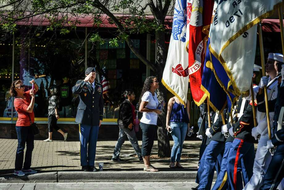 First Sgt. Normand Paquin of the U.S. Army North, second left, salutes the color guard as they walk by during the veterans parade in downtown San Antonio on Saturday, November 8, 2014. Photo: Matthew Busch, Freelancer / © San Antonio Express-News