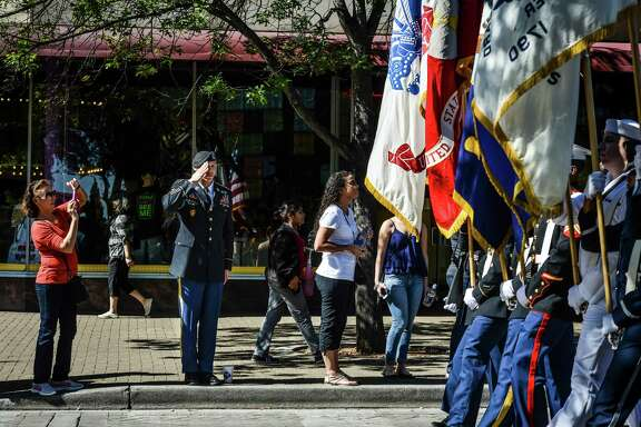 First Sgt. Normand Paquin of the U.S. Army North, second left, salutes the color guard as they walk by during the veterans parade in downtown San Antonio on Saturday, November 8, 2014.