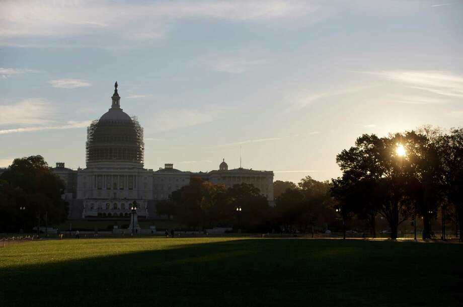 FILE - In this Oct. 20, 2014 file photo. the sun rises behind the Capitol Building  in Washington. Congress returns to Washington this week for a lame duck session to try cleaning up a lengthy roster of unfinished business, even as jubilant Republicans prepare to take over the Senate for the first time in eight years come January. (AP Photo/Carolyn Kaster, File) Photo: Carolyn Kaster, STF / AP