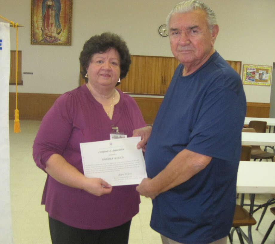 Sandra Aviles, the benefits counselor with the Bexar Area Agency on Aging, receives a certificate from veteran Abel Hernandez, a longtime member of the National Active and Retired Federal Employees association. Photo: NARFE