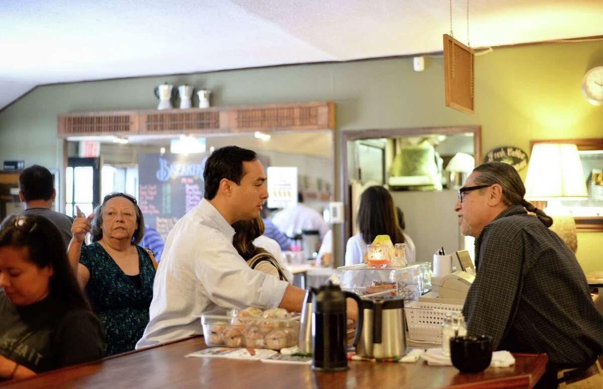 U.S. Rep. Joaquin Castro, D-San Antonio, talks with Gilbert De Hoyos, owner of Barrio Barista & Bargains, at the official opening of the West Side coffeehouse, 3735 Culebra Road, on Nov. 3. ItÆs the same building where De Hoyos' father owned a neighborhood grocery store for many years. At left is CastroÆs mom, Rosie Castro, a longtime West Side activist.