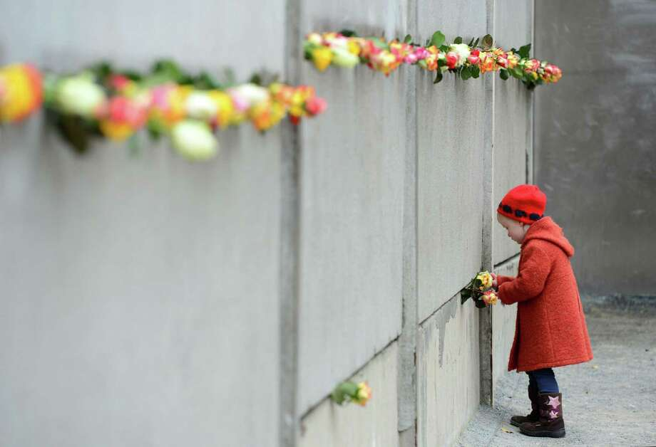 A young girl slips a rose in a preserved segment of the Berlin Wall during the commemorations to mark the 25th anniversary of its fall at the Berlin Wall Memorial in Berlin on Sunday. Photo: JOHN MACDOUGALL / JOHN MACDOUGALL / AFP/Getty Images / AFP