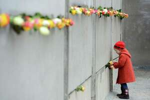 A young girl slips a rose in a preserved segment of the Berlin Wall during the commemorations to mark the 25th anniversary of its fall at the Berlin Wall Memorial in Berlin on Sunday.