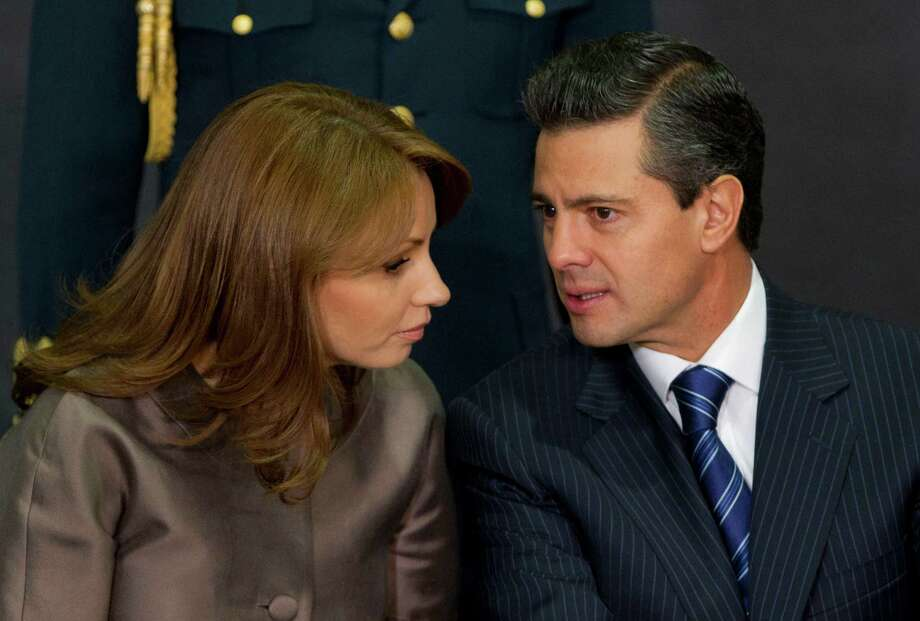 "FILE - In this March 13, 2013 file photo, Mexico's President Enrique Pena Nieto, right, speaks to his wife Angelica Rivera as they attend a ceremony launching the program ""Life insurance for female heads of family"" at Los Pinos presidential residence in Mexico City. Pena Nieto is facing a rising tide of angry protests over the disappearance of 43 students and increasingly sharp questions about his wife's purchase of a Mexico City mansion from a company that had won juicy contracts from him. (AP Photo/Eduardo Verdugo, File) Photo: Eduardo Verdugo, STF / AP"