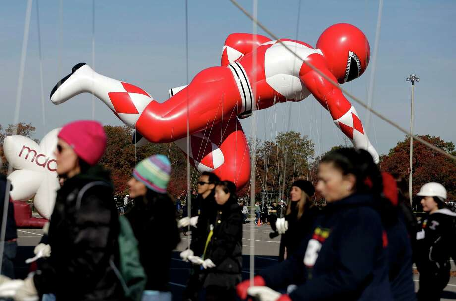 The Red Mighty Morphin Power Ranger balloon floats above the parking lot at CitiField as it is guided through a practice run by its handlers, Saturday, Nov. 8, 2014, in New York. The balloon will be one of six new characters making its debut at the 88th Annual Macy's Thanksgiving Day Parade including Pikachu, Pillsbury Doughboy, Skylanders Eruptor, Thomas the Tank Engine and Paddington.  (AP Photo/Julie Jacobson) Photo: Julie Jacobson, STF / AP