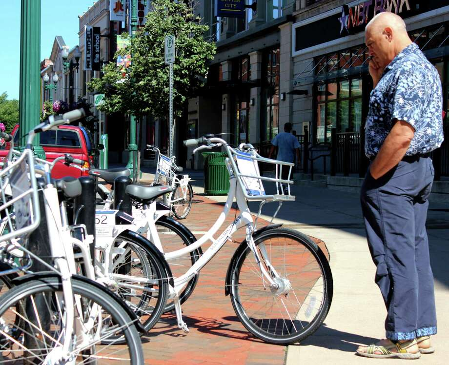 JP Martin of Amsterdam shows interest in the free bikes for rent as part of the bike share program by the Capital District Transportation Committee on Thursday, July 10, 2014, on State St. in Schenectady, N.Y. The bikes where brought to Schenectady to test public interest in creating a bike-sharing program in the Capital Region's four cities. Week-long tests will be conducted throughout the Capital Region: July 20 to 26 at Riverfront Park in in Troy, July 30 to Aug. 5 on Division Street in Saratoga Springs and Aug. 9 to 15 at Washington Park in Albany. The Capital District Transportation Committee is paying just under $50,000 to Buffalo Bike Share to run the program. (Selby Smith/Special to the Times Union) Photo: Selby Smith / 00027661A