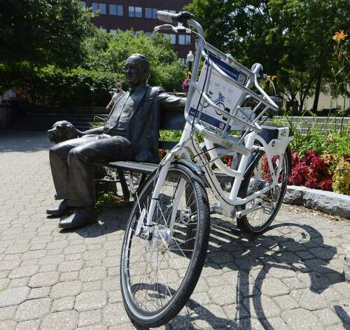 One of the bicycles available to share during the City's Bikeshare Week is locked to a bench next to a sculpture of Mayor Thomas Whalen III Monday, Aug. 11, 2014, at Tricentennial Square in Albany, N.Y. The rental is free, although participants will need to register with a credit card in order to use one the bikes. The registration locations are Washington Park, near the intersection of Hudson Ave and Washington Park Rd, on Tuesday and at Tricentennial Square Wednesday through Friday this week. Once registered you can unlock and use any of the bikes this week by means of a personal ID code entered into the bicycles locking system. The pilot program is sponsored by the Capital District Transportation Committee (CDTC). Schenectady, Troy and Saratoga Springs also took part in the bike share. (Will Waldron/Times Union) Photo: WW / 00028107A