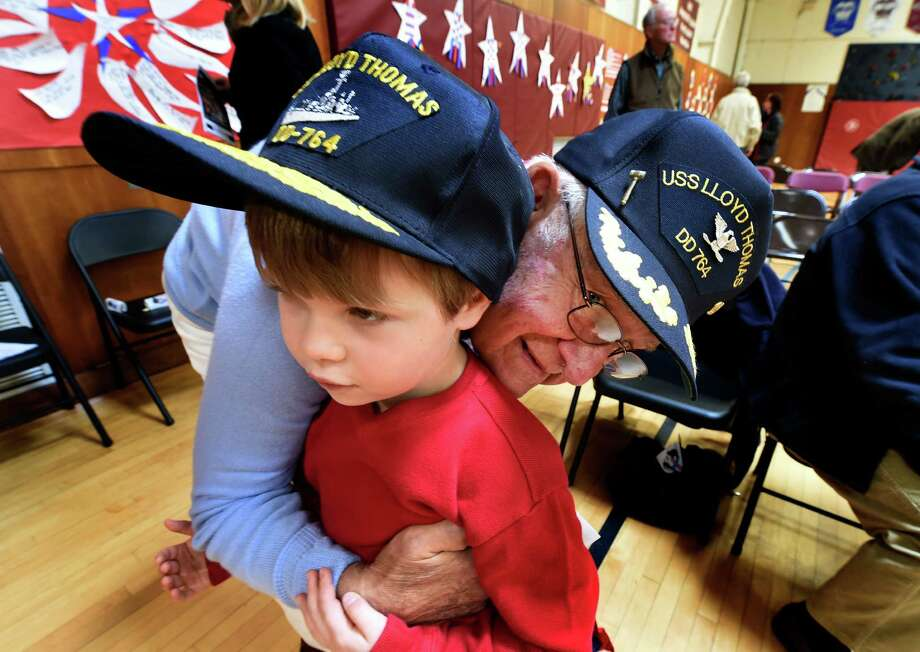 Jackson Oakes, 4, gets a baseball cap and a hug from his step-grandfather, Korean War veteran Capt. Thomas Miller (U.S. Navy Retired), after the conclusion of the Veterans Ceremony Monday morning Nov. 10, 2014 at Brown School in Schenectady, N.Y.       (Skip Dickstein/Times Union) Photo: SKIP DICKSTEIN / 00029415A