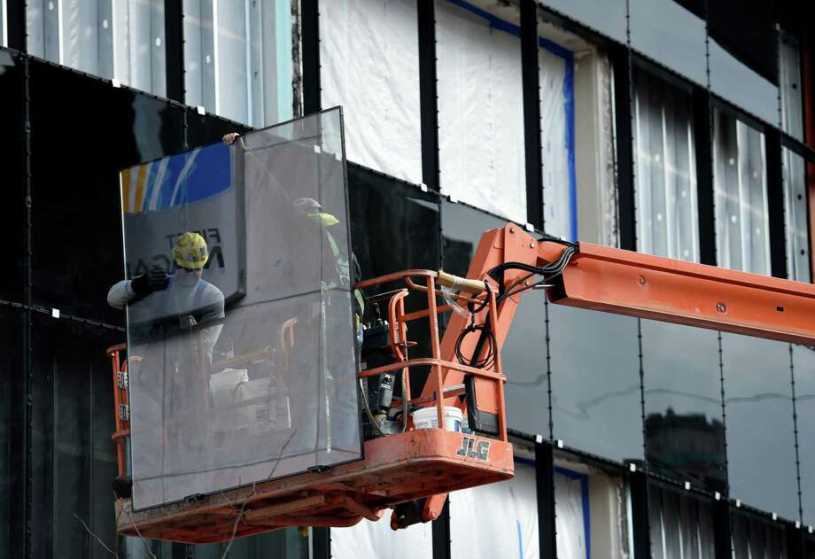 Workers from the American Glass and Metal Company work on the facade replacing glass panels Monday morning Nov. 10, 2014 at 251 State Street in Schenectady, N.Y. as the building is being renovated to house a business incubator.      (Skip Dickstein/Times Union) Photo: SKIP DICKSTEIN / 00029418A