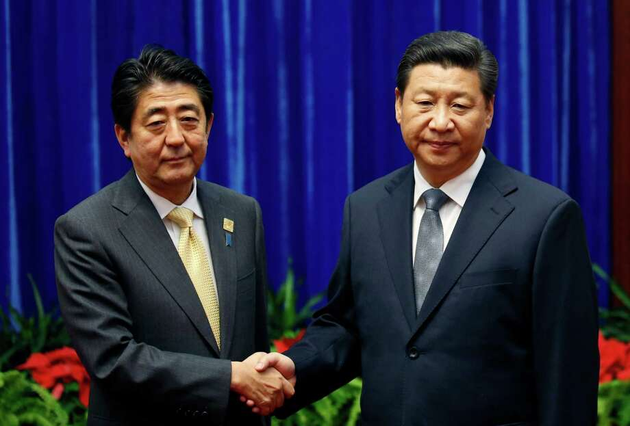 Japan's Prime Minister Shinzo Abe, left, and China's President Xi Jinping, right, shake hands during their meeting at the Great Hall of the People, on the sidelines of the Asia-Pacific Economic Cooperation (APEC) summit, in Beijing, Monday, Nov. 10, 2014. An uneasy handshake Monday between Xi and Abe marked the first meeting between the two men since either took power, and an awkward first gesture toward easing two years of high tensions. (AP Photo/Kim Kyung-Hoon, Pool) Photo: Kim Kyung-hoon, POOL / POOL REUTERS