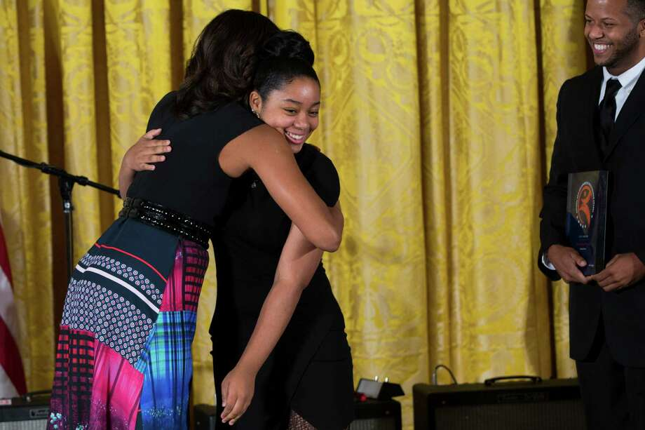 "First lady Michelle Obama hugs Brianna Burns, 13, of the ""Workshop Houston, Middle School Program,"" of Houston, as co-director Reginald Hatter looks on during an event to present the 2014 National Arts and Humanities Youth Program Awards in the East Room of the White House, on Monday. Photo: Evan Vucci, STF / AP"
