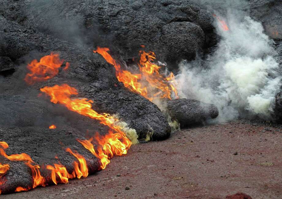 This Nov. 9, 2014 photo provided by the U.S. Geological Survey shows the lava flow from the Kilauea Volcano that began on June 27 as it burns along Cemetery Road and Apa?a Street near the town of Pahoa on the Big Island of Hawaii. A small flow of lava moved closer to a now-closed refuse transfer station on Hawaii's Big Island, but the main area of the molten rock hasn't crept any closer to the small town of Pahoa, the U.S. Geological Survey said Sunday, Nov. 9, 2014. (AP Photo/U.S. Geological Survey) Photo: HOPD / U.S. Geological Survey
