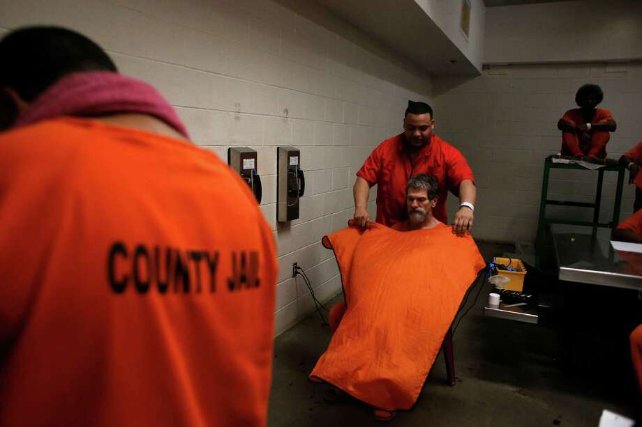 Air Force veteran and current Harris County Jail inmate, Kevin Coffman, 59, gets his haircut by inmate barber, Mark Guillory, as the Harris County Jail Stars and Stripes program members received haircuts in their cellblock for Veteran's Day Monday, Nov. 10, 2014, in Houston. The Stars and Stripes program aids about 30 jailed, rehabilitating veterans through a 90-day program where organizations such as the VA, U.S. Veterans Initiative give inmates skills and information they need about veterans benefits, through financial classes, and court representation. ( Johnny Hanson / Houston Chronicle ) Photo: Johnny Hanson, Staff / © 2014  Houston Chronicle