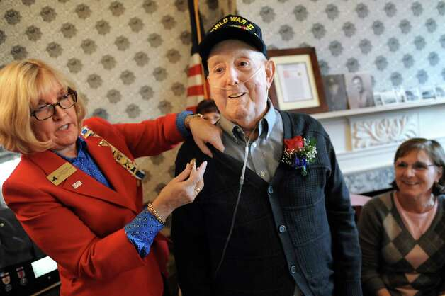 Susan Hare, regent of Gen. Peter Gansevoort Chapter of DAR, left, honors WWII veteran Ted Tornesello, center, with a pin during a Daughters of the American Revolution ceremony on Saturday, Nov. 8, 2014, at the Van Schaick Mansion House in Cohoes, N.Y. His daughter Re Getty, right, joins him. (Cindy Schultz / Times Union) Photo: Cindy Schultz / 00029410A