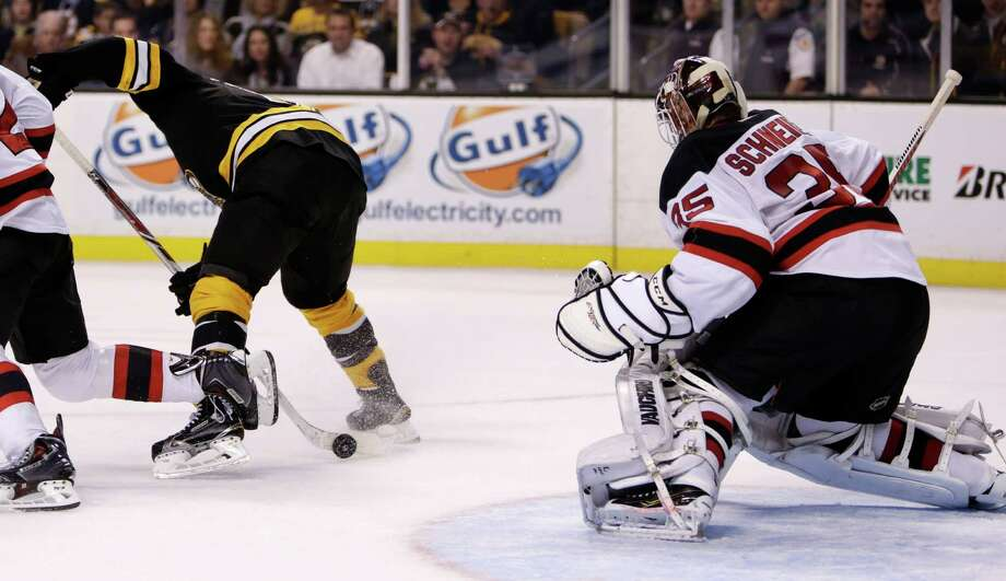 Boston Bruins center Seth Griffith, left, skates backwards as he pokes the puck between his legs, which then slid through the pads of New Jersey Devils goalie Cory Schneider (35) for a goal during the second period of an NHL hockey game in Boston, Monday, Nov. 10, 2014. (AP Photo/Charles Krupa) ORG XMIT: MACK105 Photo: Charles Krupa / AP