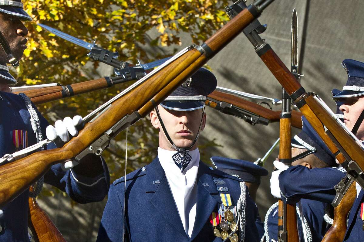 U.S. Air Force honor guard Captain Alan Marford, center, walks through a tunnel of twirling bayonnet rifles during a drill performed at the National September 11 Memorial and Museum's