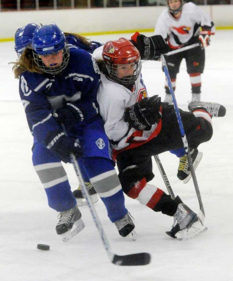 Darien's Lily Christensen battles with Greenwich's Hannah Jeffrey as Darien hosts Greenwich High in a girls hockey game at the Darien Ice Rink Wednesday evening, Feb. 24, 2010. Photo: Keelin Daly / Greenwich Time