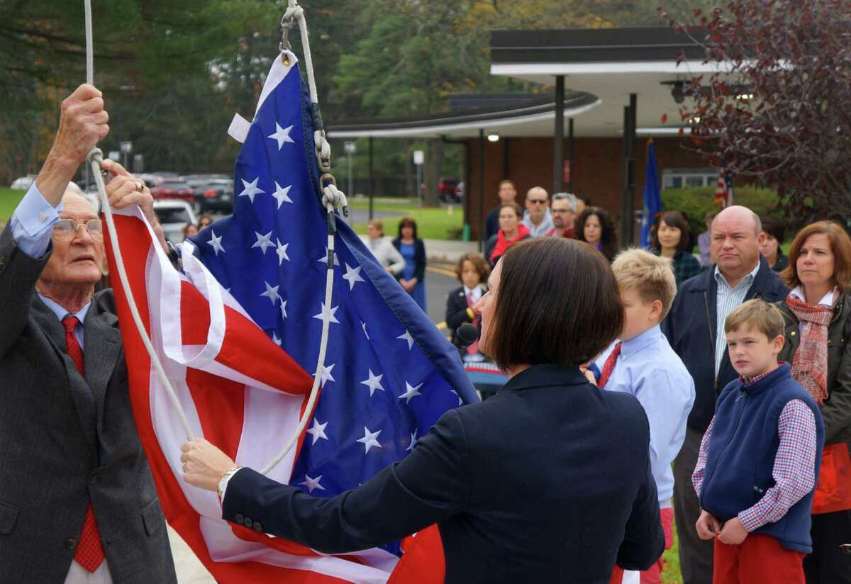 Retired Lt. Gen. Robert E. Pursley, who served in the Korean and Vietnam Wars, raises the flag with North Street School Principal Jill Flood, during the school's Veterans Day ceremony on Tuesday. At right, Pursley's grandsons, Kieran and Daniel, look on, with their parents, Don and Carol McGuire.