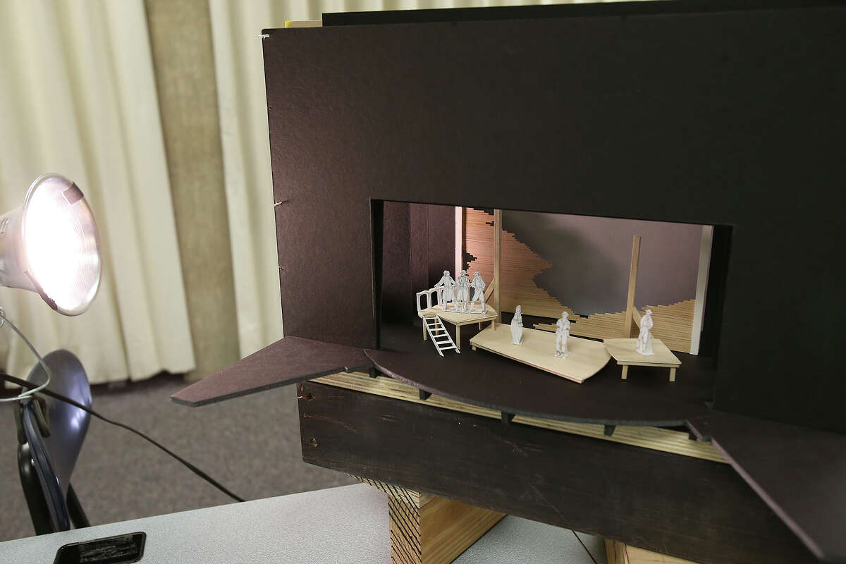 The set mockup is displayed as Virgil Johnson works on the costume designs for Trinity University's staging of the play