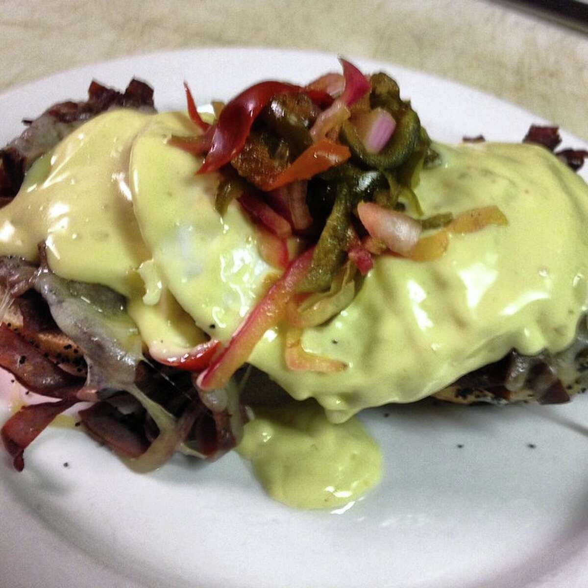 Frank's open face Kaiser roll with griddled roast beef, easy eggs, white cheddar, macerated cherry pepper, red onion, hollandaise and bacon snow.